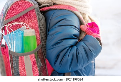 Pink backpack with hand sanitizer (hand rub) and medical face shield. The briefcase is not on the child's back. Back to school. Prevention of viruses and diseases in children