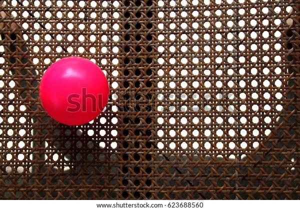 Pink ball put on rattan wicker chair