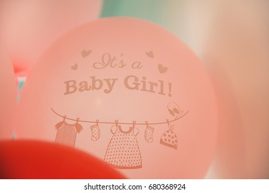 Pink balloons with baby girl sign on it