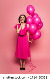 Pink balloons. Full-length photo of a happy girl in a long fuchsia dress, who is smiling with her eyes closed and holding pink balloons in her left hand.