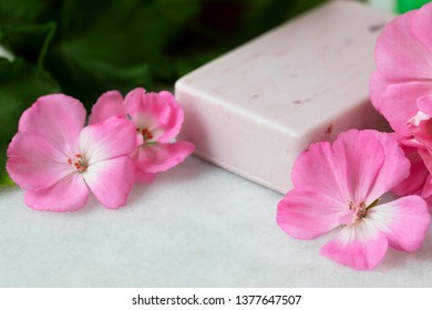 Pink bar of soap with bright pink geranium flowers.