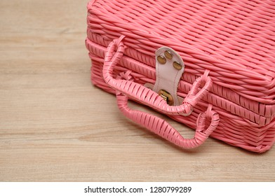 A pink basket on a wooden background