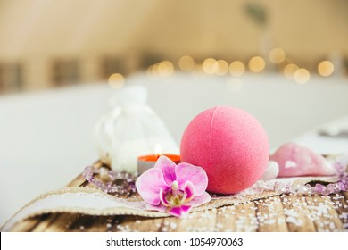 Pink bath ball with orchid flower, scented candle and bath salt on wooden tray in bath room. Therapy concept. Taking a relaxing bath.