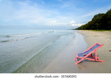 Pink beach chair at the close of the sea water.