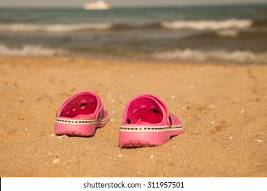 0458ea849818b1 Pink beach crocs on sandy beach.Beach flip flops in the foreground and  blurred sea