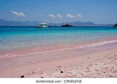Pink Beach on a lost Island in Indonesia with two boats in the background and ocean view / Komodo Islands / Labuanbajo