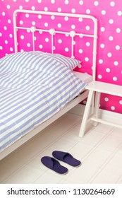 Pink bedroom with bedstead and slippers