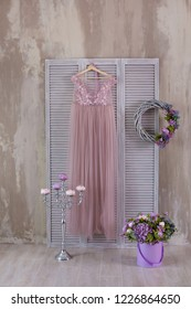 Pink and beige colored studio decorations. Silver sconce candelabrum standing on wooden floor close to wood screen with beige airy stylish dress.