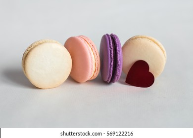 pink, beige and purple macaroon lying on a light background with red heart, desserts for Valentine's day, be my Valentine, gifts for Valentine's Day