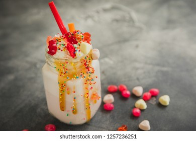 Pink berry milkshake with whipped cream, dripping sauce and candy's on table
