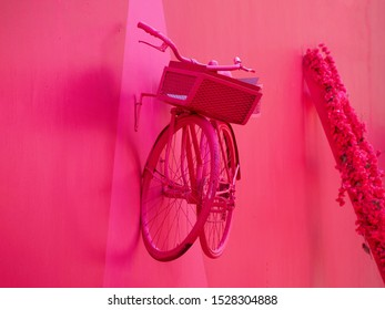 Pink bicycle with a basket hanging on a pink wall.