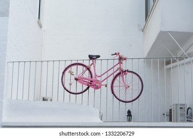 Pink bicycle hanged on a white background