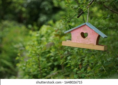 Pink birdhouse with blue roof and heart shaped entrance