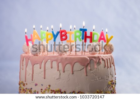 Pink Birthday Cake With Candles Coconut Balls And Sprinkles On Light Blue Background