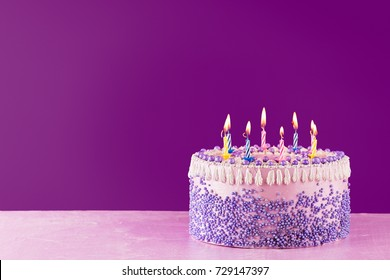 Pink Birthday cake with colorful candles over a bright purple background with copy space