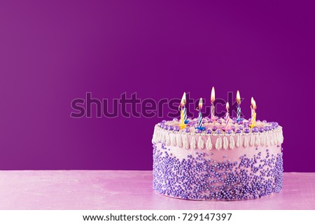 Pink Birthday Cake With Colorful Candles Over A Bright Purple Background Copy Space