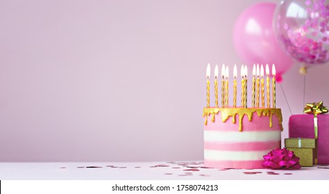 Pink birthday cake with golden candles and balloons
