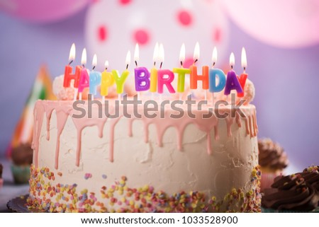 Pink Birthday Cake With Happy Candles And Colorful Baloon Background