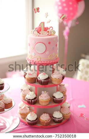 Pink Birthday Cake On Top Of A Tiered Stand With Chocolate And Strawberry Cupcakes