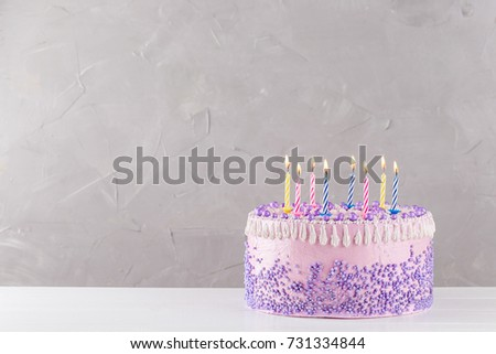 Pink Birthday Cake With Purple Sprinkles And Colorful Candles Over Gray Background Copy Space