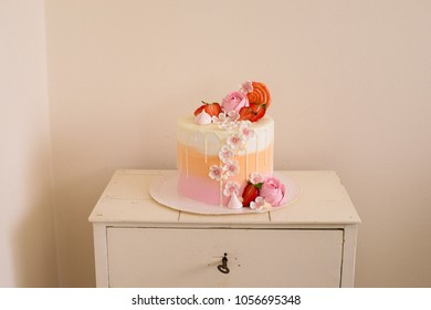 Pink birthday cake with strawberries and roses