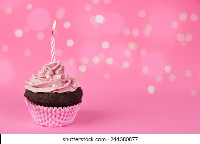 Pink birthday cupcake with a candle and lights effect at the background