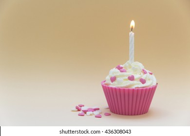 pink birthday cupcake with candle and suggar hearts