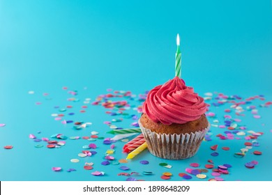 Pink birthday cupcake with green candle and confetti on blue background. Copy space