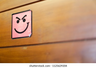 Pink and black smile sticker on a wooden door