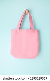 pink blank tote bag mock up design on blue background hanging on wooden hanger