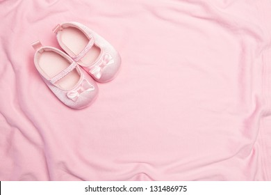 Pink blanket and baby slippers with copy space