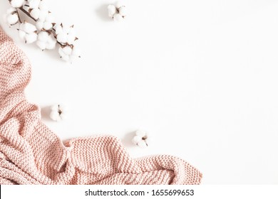 Pink blanket, cotton flowers on white background. Flat lay, top view, copy space
