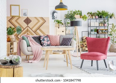 Pink blanket and patterned cushions on sofa near red chair and wooden table in floral living room interior
