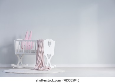 Pink blanket and pillow in white cradle against a wall with copy space in white baby's bedroom interior with rug