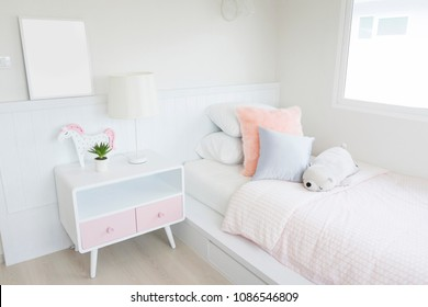 Pink blanket and pillows on bed in colorful kids room with cute doll and side table.
