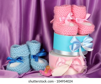 pink and blue baby boots, pacifier and gifts on silk background