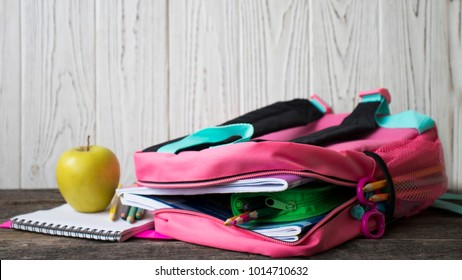 Pink and blue backpack with school supplies including paint, pencils, pens, markers, erasers and apple on wooden background