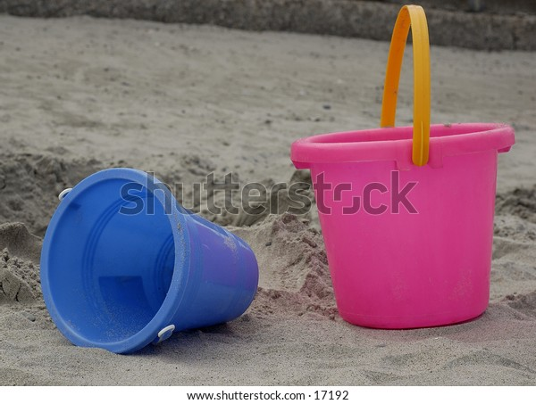 Pink and blue buckets in the sand