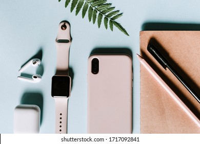 Pink and blue flat lay home office with modern gadgets such as smartphone, smartwatch, earphones, notepad, pen. Pink and blue colors. Copyspace to write. Minimalist style to enhance productivity
