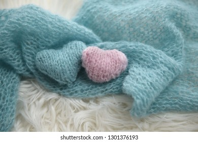 Pink and blue hand knit hearts on blue knit shawl