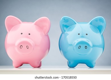 A pink and a blue piggy bank standing next to each other. Closeup front view.