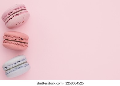 Pink, blue, red, lavender macaroons on the pastel pink background. Place for text. Festive concept.