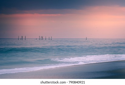 Pink and blue skies over the horizon on the beach with waves in the Atlantic Ocean. Taken in Myrtle Beach, South Carolina