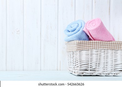 Pink and blue towel on white wooden table