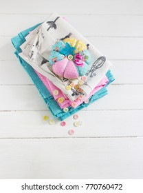 Pink blue white fabrics pumpkin pin cushion wooden table.