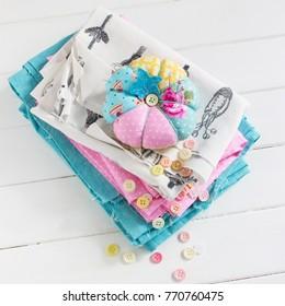 Pink blue white fabrics pumpkin pin cushion wooden table square.