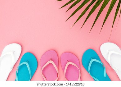 Pink, blue, white flip flops shoes on pink background, top view, copy space. Toe sandals, flat lay, text place. Summer background with flipflop shoes and palm leaves.