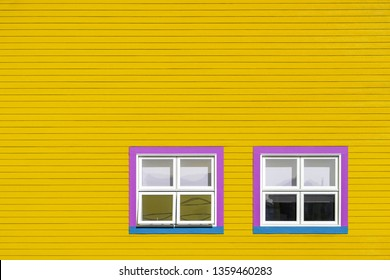 Pink, blue and white windows on a yellow wooden wall. Minimalism style of the houses of Iles de la Magdalen, Canada, in bright colours with space for text.