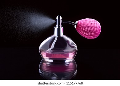 Pink bottle of perfume spraying, isolated on black background