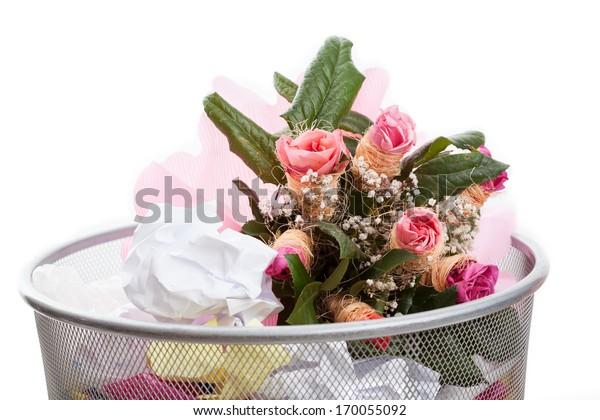 A pink bouquet of flowers in a dustbin